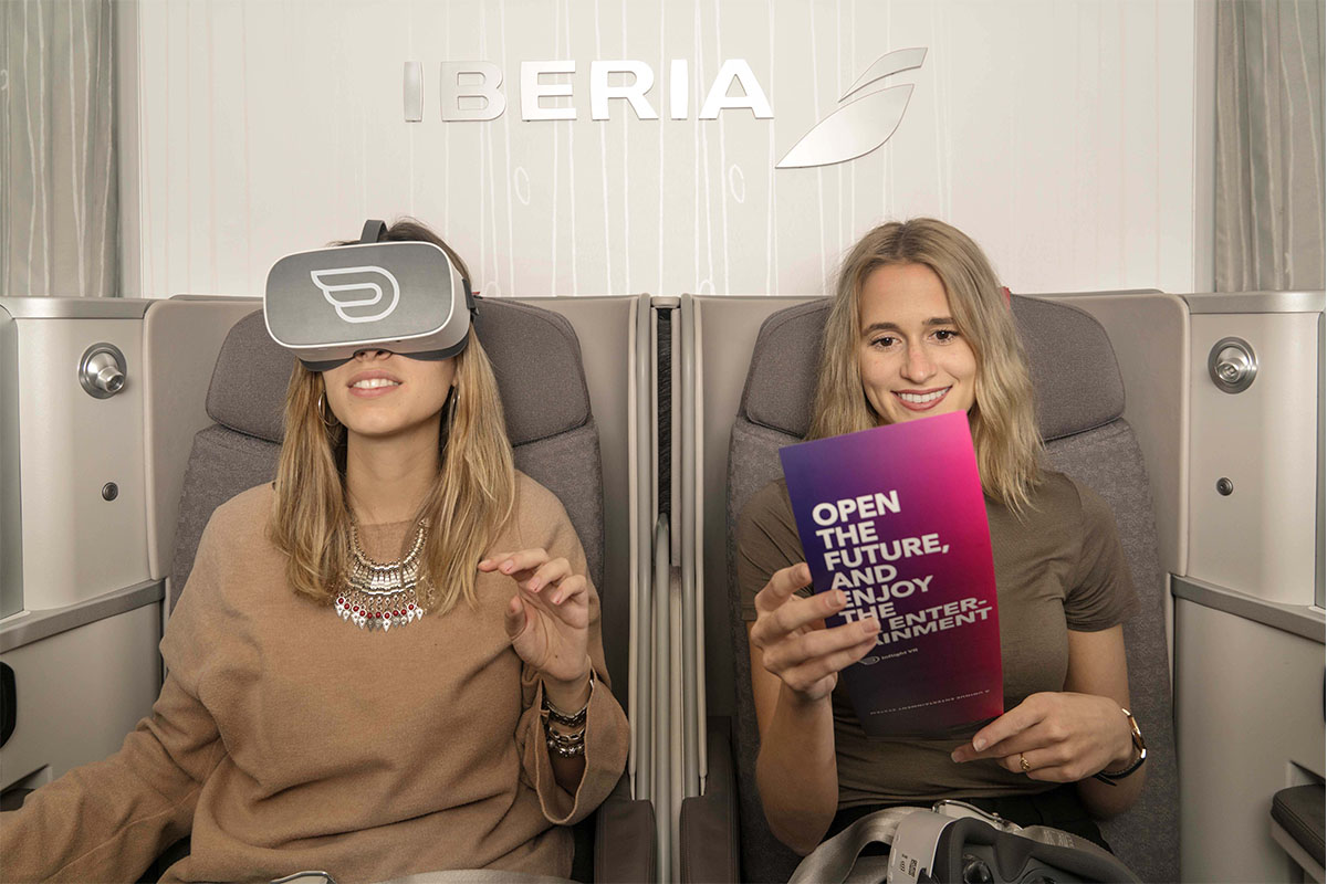 Two womens inside Iberia's cabin having inflight vr experience