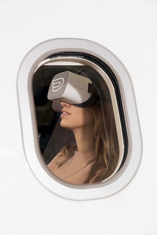 Women on an Iberia plane with pico headset having a VR experience
